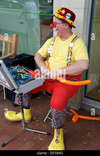 Jolly middle-aged male clown making balloon hats, Vancouver, British Columbia, Canada - Stock Image