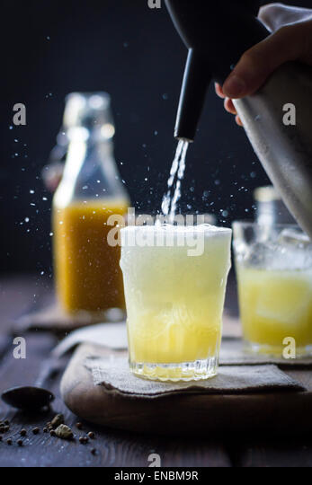 A Mumbai Mule cocktail in a glass on a wooden background. - Stock Image