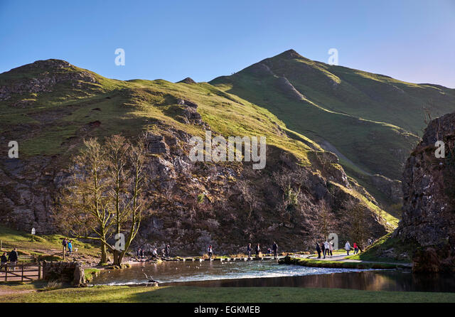 People on the famous Stepping Stones across the River Dove in Dovedale with Thorpe Cloud beyond. Ilam, Derbyshire, - Stock Image