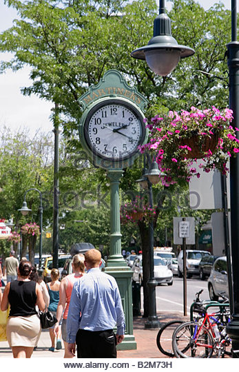 Michigan Traverse City Front Street shopping pedestrians man woman women walk historic clock street lamp - Stock Image