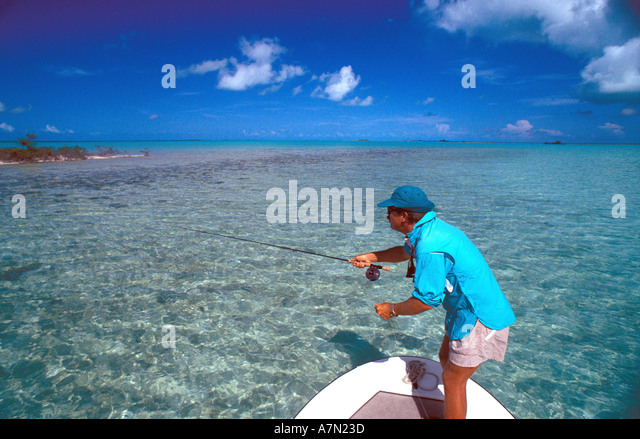 salt water fly fishing angler casting to fish blue sky background - Stock Image