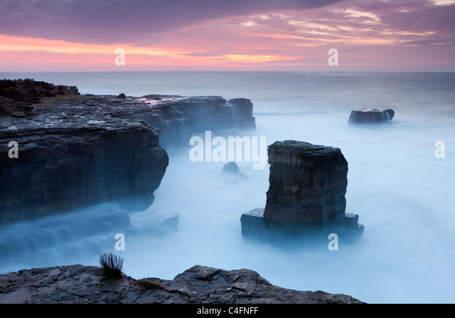 Beautiful sunrise over the rocky coast of Portland Bill on the Jurassic Coast, Dorset, England. Winter (February) - Stock Image
