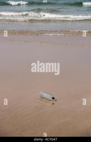 Plastic bottle polluting a sandy beach - Stock Image