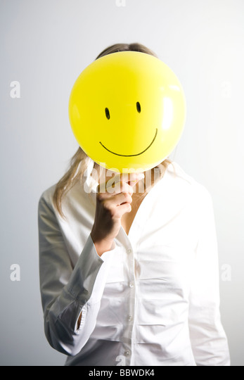 woman-holding-balloon-with-smiley-face-i