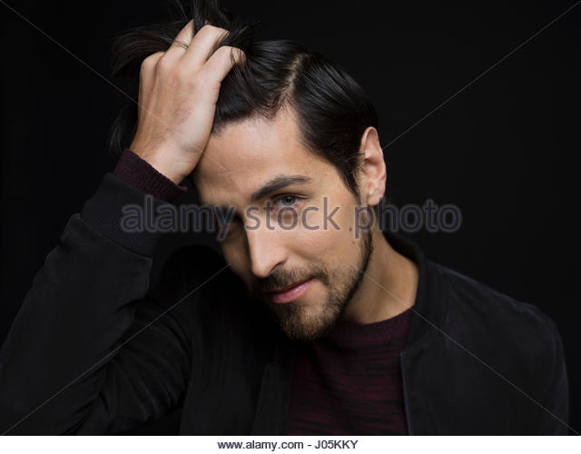 Portrait handsome brunette man with b beard and hand in hair against black background - Stock Image