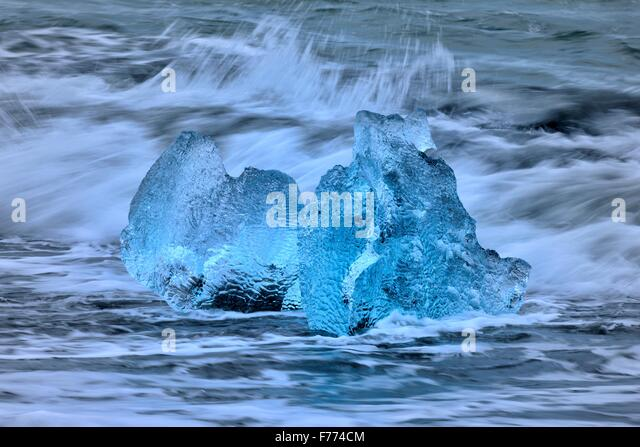 Beached blue icebergs in the surf of the Atlantic, Breidarsandur, South Iceland, Iceland - Stock Image