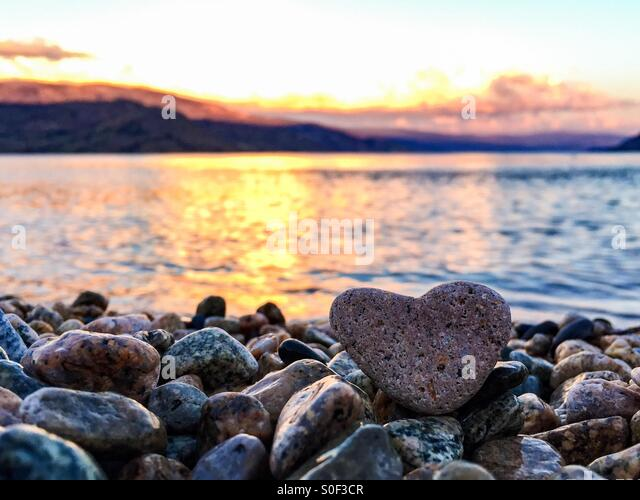 Summer love. Heart shaped rock on the beach with lake and mountains in the background at sunset offer a romantic - Stock-Bilder