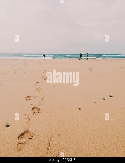 Three people on a beach - Stock Image