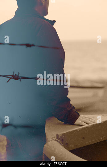 Double exposure of a man and barbed wire - Stock Image