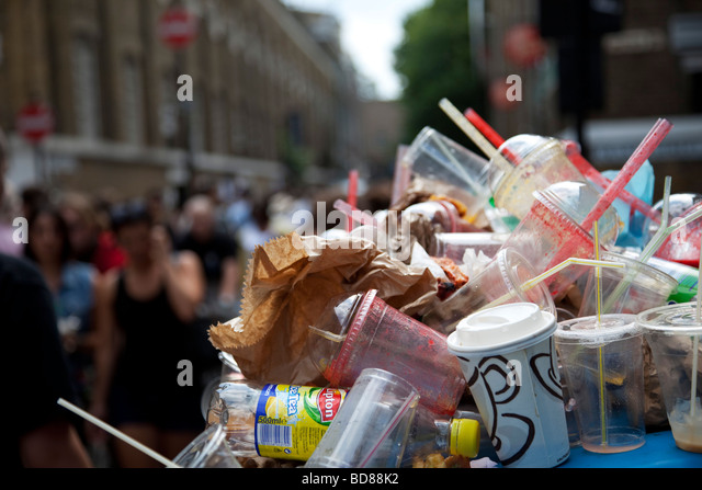 Rubbish overflows the bins on Brick Lane Market. Extreme amounts of plastic and paper trash litter the streets. - Stock Image