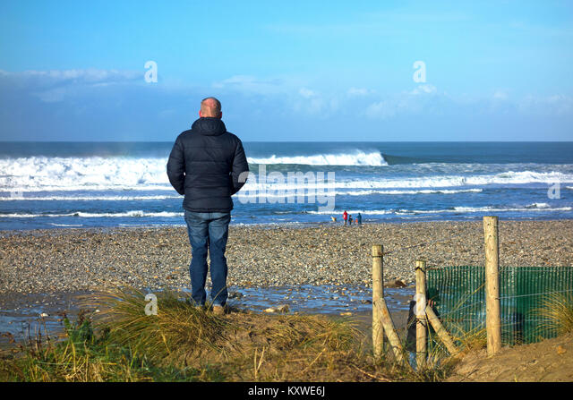 man alone looking out to sea at porthtowan, in cornwall, england, britain, uk. - Stock Image