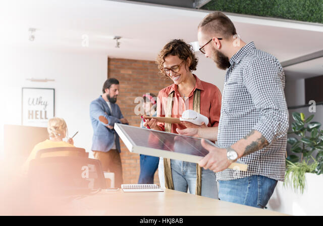 Smiling design professionals reviewing storyboard in office - Stock-Bilder