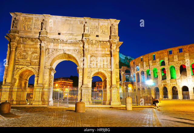 View of the Arch of Constantine and Colosseum at night in Rome, Italy - Stock Image