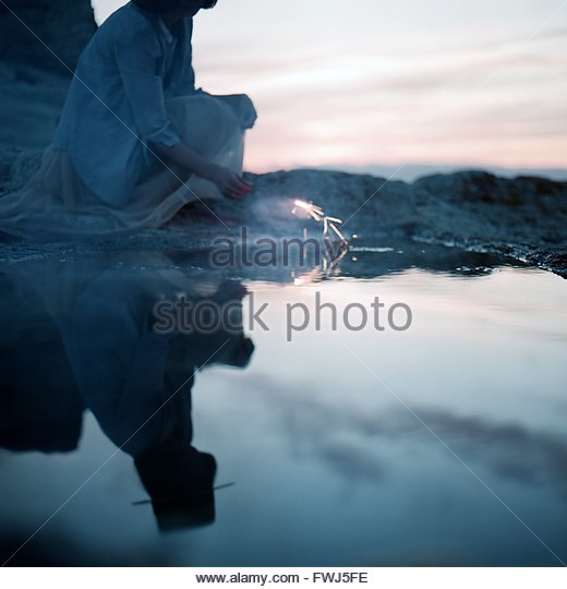Reflection Of Woman Holding Sparklers - Stock Image