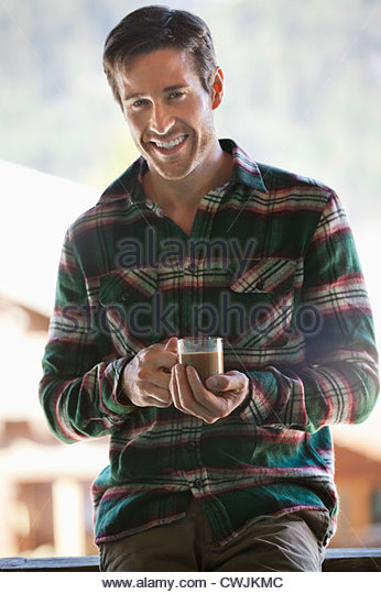 Portrait of smiling man drinking coffee - Stock Image