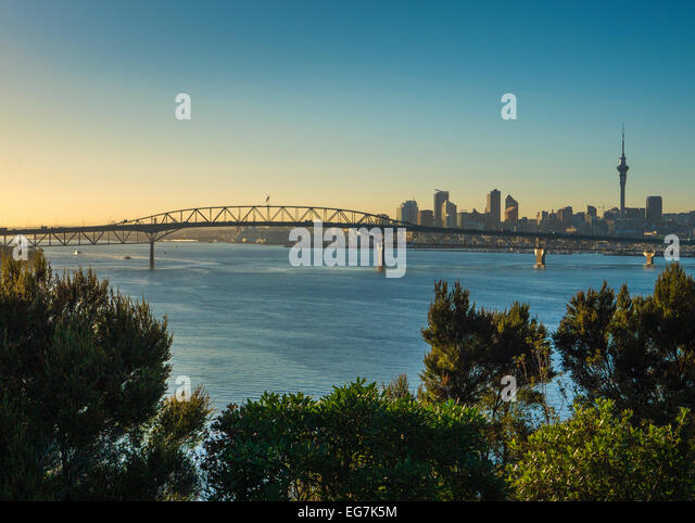 Auckland harbour bridge and Auckland city at sunrise from the north shore - Stock Image