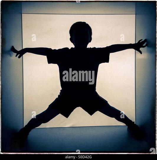 Silhiuette of a kid inside a giant cube - Stock Image