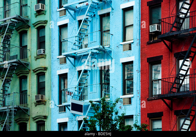 Three colorful, red, blue and green, apartment buildings facades with emergency escapes. Typical New York City, - Stock Image
