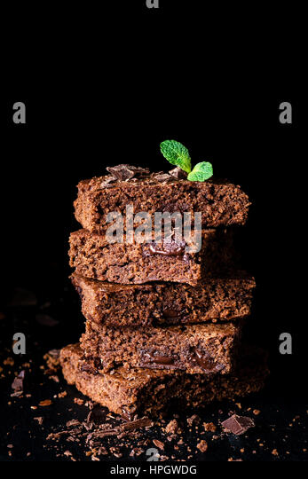 Stack of brownies with dark chocolate over black background, closeup view, vertical composition - Stock Image