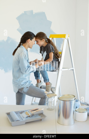 Mother and daughter painting wall blue - Stock Image