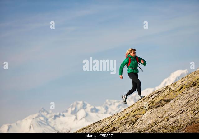 A jogger running over rocky mountains. - Stock-Bilder