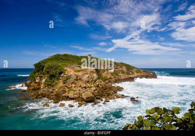 Rocky island in surf off the north east coast of Puerto Rico - Stock Image