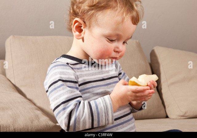 Little boy eating pear - Stock Image