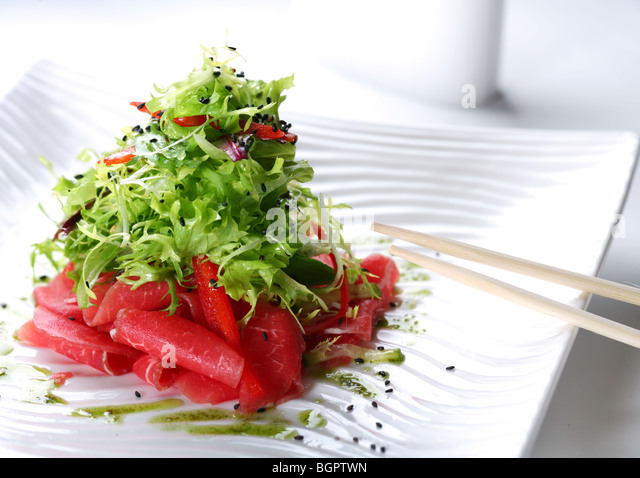 salad with arugula and raw beef on a white plate - Stock Image