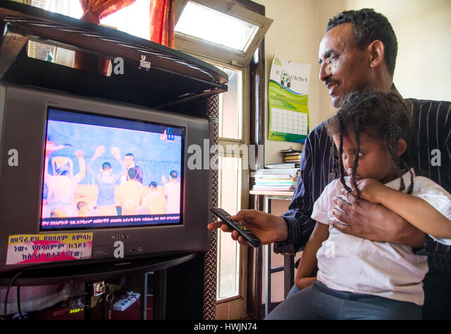 Pastor Mohamed Ousman Salih who converted from islam to christianity watching a religious channel on television - Stock-Bilder