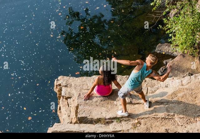 Young couple throwing stones from rock ledge, Hamburg, Pennsylvania, USA - Stock-Bilder