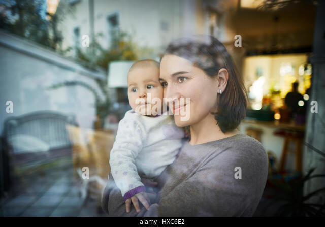 Smiling mother holding baby daughter at window - Stock Image