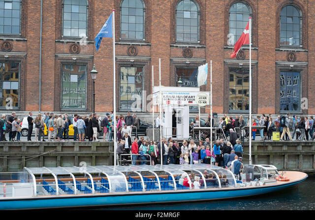 Tourists taking a canal trip at Nyhavn New Harbour Copenhagen Denmark - Stock Image