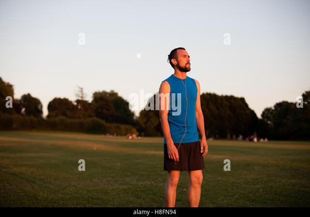Young athletic man resting after a run in the park - Stock Image