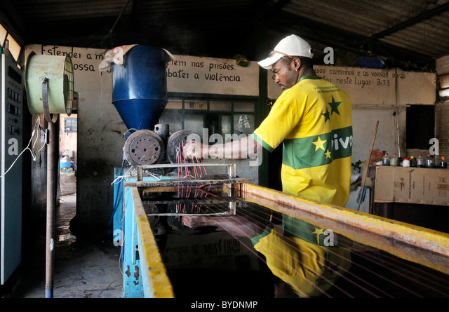 Worker at the process of melting and re-hardening used plastics in the social project for ex-prisoners 'Reintegar - Stock Image