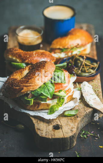 Breakfast with bagels with salmon, avocado, cream-cheese, basil, espresso coffee, capers on rustic wooden board - Stock Image