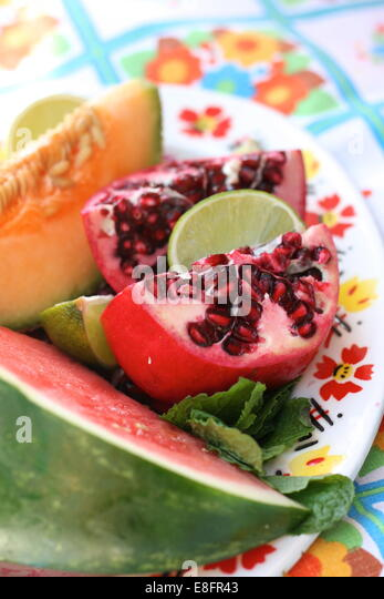 Plate full of summer fruits including melons and pomegranate on vintage plate - Stock Image