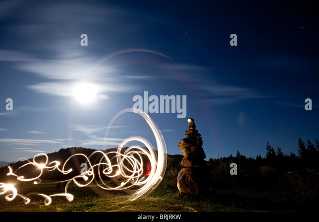 Rock cairn with light painting next to it and full moon in background in Idaho. - Stock Image