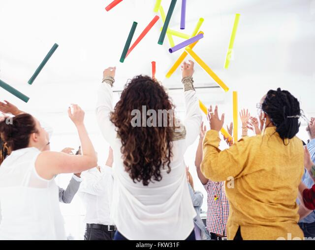 Rear view   colleagues in team building task throwing colourful tubes in the air - Stock Image