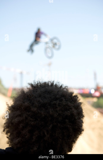 close up of back of man heads sporting afro hair watching bicylcist jumping in mid air - Stock Image