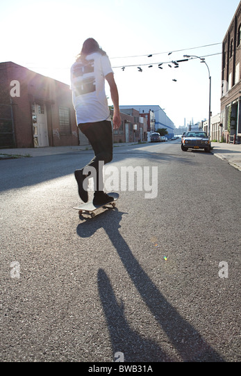 Skateboarder on urban street in sunlight - Stock-Bilder