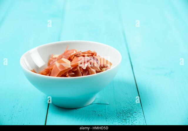 Fresh Bacon In White Bowl On Turquoise Table - Stock Image