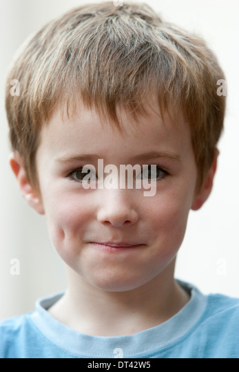 Portrait of a timid looking young boy - Stock Image
