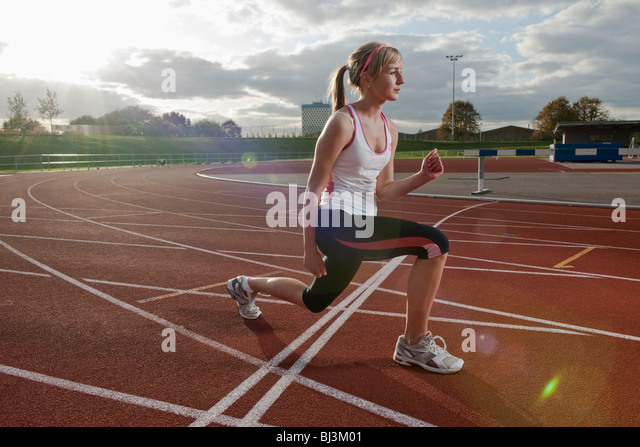 female athlete stretching leg muscles - Stock Image