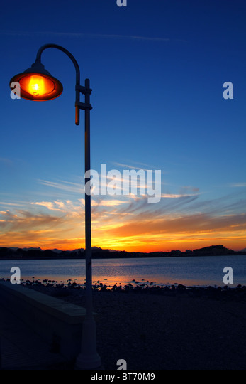 Sunset orange blue seascape light lamppost Mediterranean Denia alicante spain - Stock Image