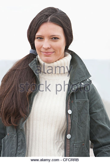 Portrait of smiling young woman in warm clothing - Stock Image