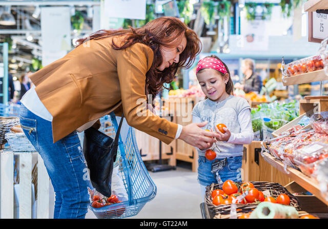 Mother and daughter buying tomatoes in supermarket - Stock-Bilder
