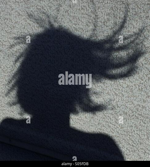 Woman's shadow showing wind blowing her hair on a boat ride - Stock Image