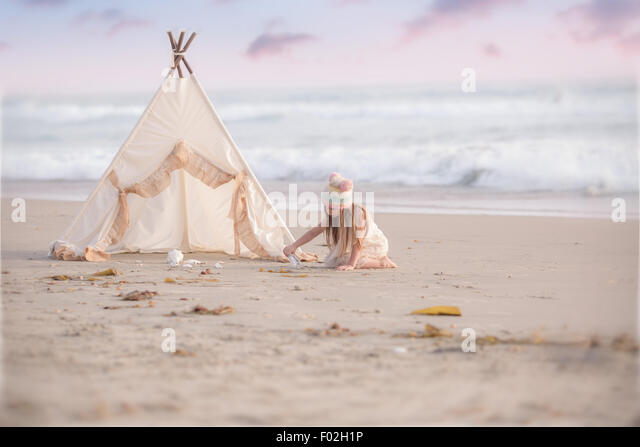 Girl sitting by a wigwam on the beach digging sand - Stock Image