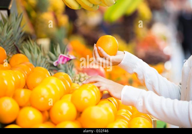 Female close-up hand apple orange - Stock Image