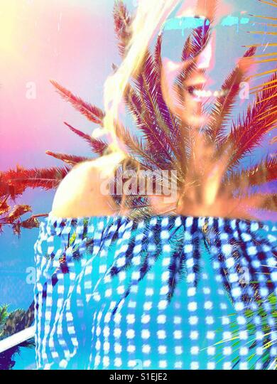 Double exposure edit of smiling woman wearing sunglasses and palm trees with a sunny sky. - Stock Image